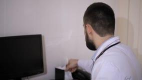 O doutor masculino que fala ao paciente no hospital e prescreve comprimidos filme