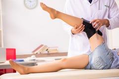 O doutor masculino que verifica a flexibilidade comum com o goniômetro foto de stock
