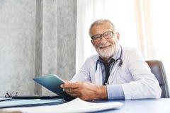 O doutor masculino superior está sorrindo em uma sala médica imagem de stock