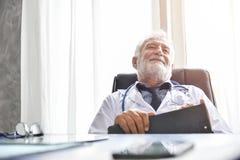 O doutor masculino superior feliz está pensando fotos de stock
