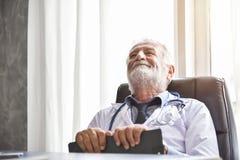 O doutor masculino superior feliz está pensando imagem de stock