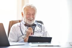 O doutor masculino superior feliz está verificando seus informes médicos pacientes fotos de stock