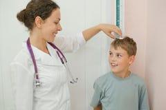 O doutor mede o menino do crescimento no escritório médico Imagens de Stock