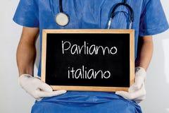 O doutor mostra a informação no quadro-negro: nós falamos italiano Conceito MÉDICO fotografia de stock
