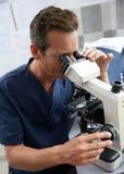 O doutor na fatura do laboratório analisa com microscópio Fotos de Stock Royalty Free