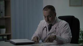 O doutor no dever de noite enche cartões dos pacientes e decide-os tomar a sesta na cadeira acolhedor filme