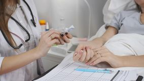 O doutor no hospital está indo dar uma injeção ao paciente O doutor desembala uma seringa descartável filme