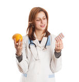 O doutor no uniforme médico faz uma escolha entre a vitamina natural Fotos de Stock