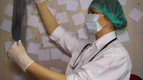 O doutor novo que veste uma máscara examina um raio X do torácico filme