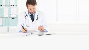 O doutor prescreve a prescrição que senta-se no escritório médico da mesa, isolado no espaço branco, da cópia e na bandeira da We fotos de stock royalty free