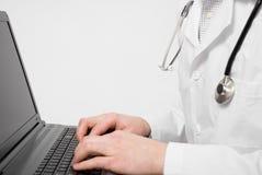 O doutor que faz algum trabalha no portátil Imagens de Stock Royalty Free