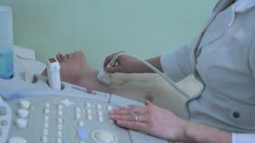 O doutor que usa a ecografia do ECO examina o fim humano da glândula de tiroide acima video estoque