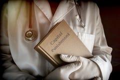 O doutor realiza em um livro de pena capital em um hospital Foto de Stock Royalty Free