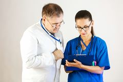 O doutor superior verifica os resultados do tratamento e das negociações do paciente a um outro doutor imagem de stock