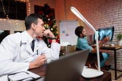 O doutor trabalha na véspera do ` s do ano novo Comunica-se com um colega que lhe mostre uma fotografia do raio X imagens de stock