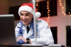 O doutor trabalha na véspera do ` s do ano novo Pôs sobre um chapéu do ` s do ano novo e falou no vídeo Imagem de Stock Royalty Free