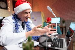 O doutor trabalha na véspera do ` s do ano novo Pôs sobre um chapéu do ` s do ano novo e falou no vídeo Imagens de Stock Royalty Free