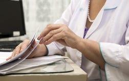 O doutor, trabalhador médico em um revestimento branco examina o docume da tabela Foto de Stock