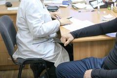 O doutor, trabalhador médico em um revestimento branco recomenda o paciente de um homem doente que senta-se em uma cadeira em uma imagem de stock