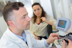 O doutor verifica os olhos pacientes usando o dispositivo oftálmico fotografia de stock