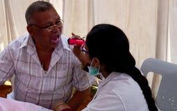 O doutor verifica a saúde oral de um paciente que usa a luz da tocha fotografia de stock