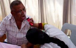O doutor verifica a saúde oral de um paciente que usa a luz da tocha para inspecionar a boca imagens de stock