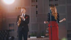 O dueto do jazz executa na fase Estilo retro do saxofonista e do vocalista dança video estoque