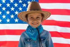 o E Счастливый ребенк, милая девушка маленького ребенка с американским флагом Ковбой стоковое изображение