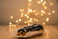 O eclair de chocolate com boken luzes no fundo foto de stock royalty free