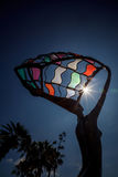 O eclipse solar parcial brilha através da estátua colorida do metal Fotos de Stock Royalty Free