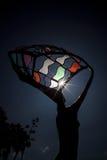 O eclipse solar parcial brilha através da estátua colorida do metal Foto de Stock Royalty Free