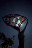 O eclipse solar parcial brilha através da estátua colorida do metal Fotografia de Stock