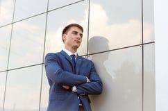 O economista bem sucedido novo do homem que está no escritório moderno interior, homem seguro vestiu-se na roupa incorporada luxu Fotografia de Stock