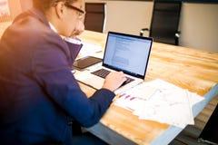 O economista masculino incorpora dados no caderno sobre o relatório mensal, sentando-se ao escritório fotografia de stock