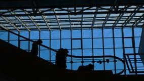 O ecsalator do aeroporto da janela de vidro com a silhueta movente dos povos vídeos de arquivo