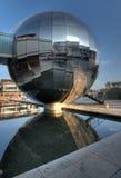 O edifício esférico espelhado reflete na água Fotografia de Stock Royalty Free