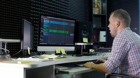 O editor audio está trabalhando na trilha audio no som do estúdio vídeos de arquivo