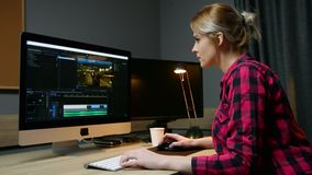 O editor video da mulher trabalha com metragem em seu computador, trabalhos no escritório Edição video, vista lateral filme
