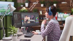 O editor video e o colorist fêmeas põem seus fones de ouvido sobre filme