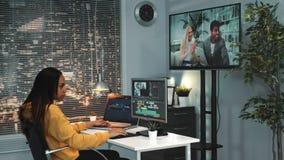 O editor video fêmea afro-americano trabalha no computador e monta o vídeo dos quadros diferentes vídeos de arquivo
