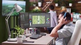 O editor video profissional na agência criativa ocupada põe fones de ouvido sobre filme