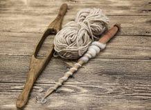O eixo dois de madeira velho com uma bola das lãs rosqueia para a fabricação de linhas de lã em um fundo de madeira Fotos de Stock
