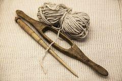 O eixo dois de madeira velho com uma bola das lãs rosqueia para a fabricação de linhas de lã em um fundo do tecido Foto de Stock Royalty Free