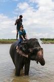 O elefante que toma um chuveiro com o turista e o motorista em chitwan, Nepal Fotografia de Stock