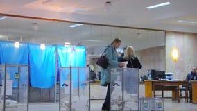 O eleitor fêmea louro põe a cédula na urna de voto Eleição do presidente de Ucrânia video estoque
