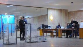 O eleitor masculino novo põe a cédula na urna de voto Eleição do presidente de Ucrânia video estoque