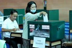 O eleitor tailandês põe uma cédula na urna de voto durante o avanço votou imagens de stock royalty free