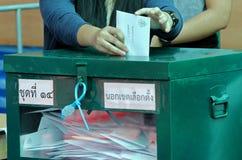 O eleitor tailandês põe uma cédula na urna de voto durante o avanço votou imagens de stock