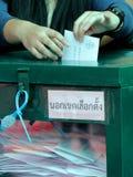 O eleitor tailandês põe uma cédula na urna de voto durante o avanço votou fotos de stock royalty free