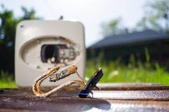O elemento de aquecimento da água danificado das mentiras da corrosão em uma tabela de madeira ao lado da caldeira Na grama verde foto de stock royalty free